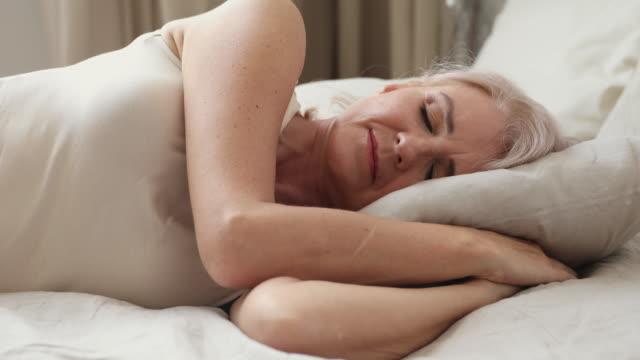 vídeos y material grabado en eventos de stock de tranquilo tranquilo feliz adulto mujer mayor durmiendo en casa. - columna vertebral humana