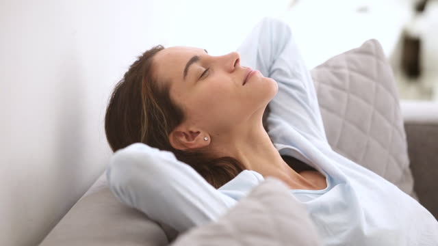 Calm relaxed young woman resting leaning on comfortable soft sofa Calm relaxed young woman resting leaning on comfortable soft sofa chilling taking healthy nap at home, serene girl breathing fresh air dreaming enjoy peaceful mood lounge feeling no stress concept resting stock videos & royalty-free footage