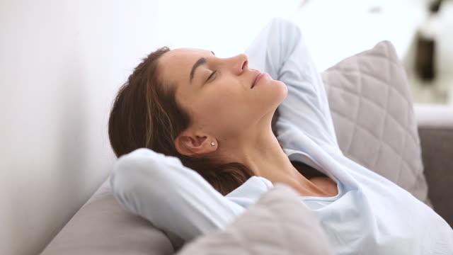 vídeos de stock, filmes e b-roll de descanso relaxed calmo da mulher nova que inclina-se no sofá macio confortável - despreocupado