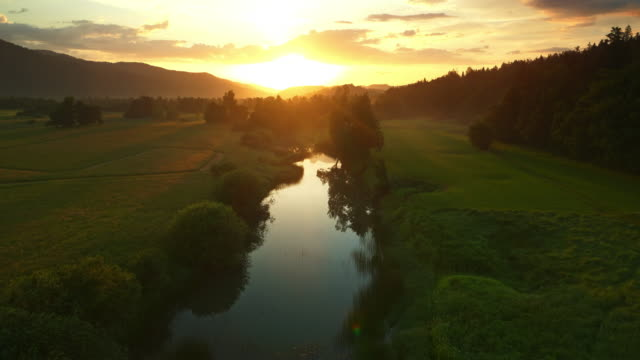AERIAL Calm river amongst the meadows at sunrise