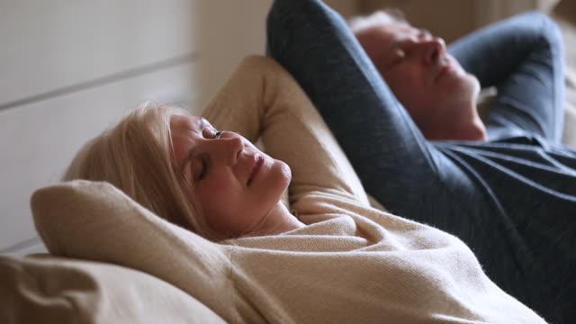 calma coppia anziana di mezza età rilassante appoggiato su comodo divano - sonnecchiare video stock e b–roll