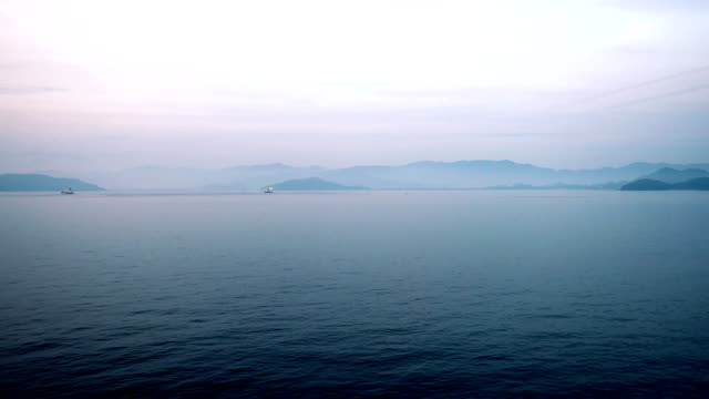 Calm serene scenery beautiful sky with colorful clouds rippled water surface reflection open sea seascape in dawn video