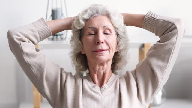 落ち着いた笑顔の年長70歳の女性は家でリラックス - 耐久力点の映像素材/bロール