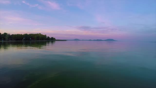 calm water on the lake balaton in hungary with old volcanoes - спокойная вода стоковые видео и кадры b-roll