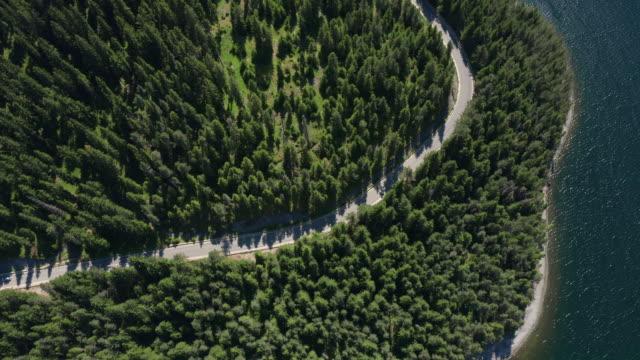vidéos et rushes de surface d'eau calme, rivage pittoresque de lac et crêtes de vue aérienne dense de forêt verte d'épinette de drone sur des pentes de montagne en été au coucher du soleil et au ciel bleu. autoroute. de l'air frais et pur. nature - mer d'andaman