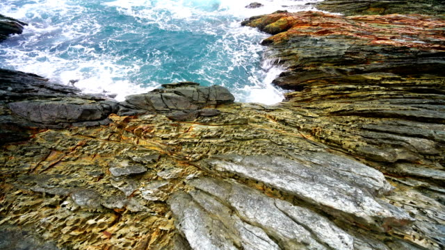 calm waves splash on rocky shore - rock formations stock videos & royalty-free footage