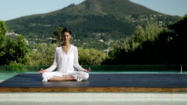 vídeos y material grabado en eventos de stock de tranquila mujer haciendo yoga junto a la piscina - balneario spa
