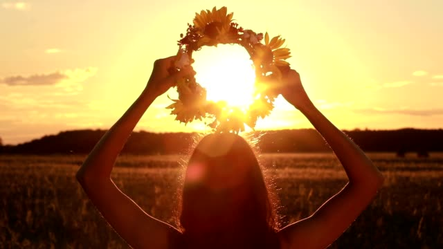 Calm woman holding flower wreath in twilight time video