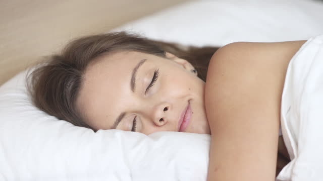 Calm woman sleeping well in comfortable bed on soft pillow