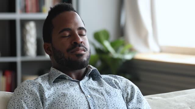 ruhiger junger afrikanischer mann meditieren auf sofa mit geschlossenen augen - atemübung stock-videos und b-roll-filmmaterial