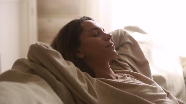 giovane donna calma che fa un pisolino sano rilassarsi sul divano - sonnecchiare video stock e b–roll