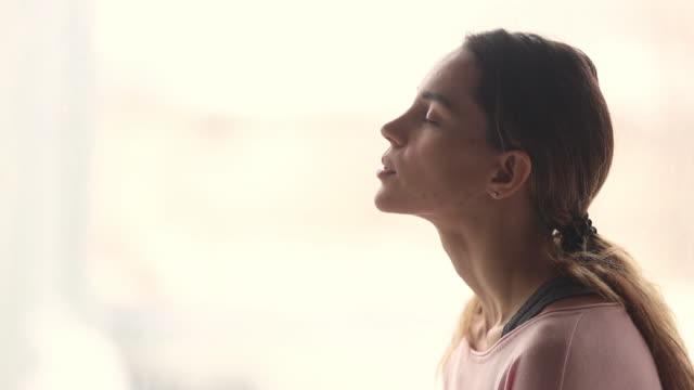 Calm young woman taking deep breath of fresh air
