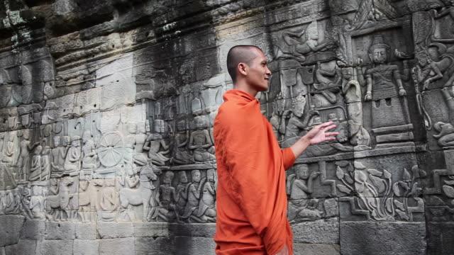 vídeos de stock, filmes e b-roll de cambojano budistas discutir bas-relevos no bayon angkor - relevo