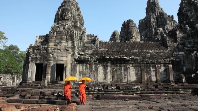 vídeos y material grabado en eventos de stock de camboyano monjes caminando en angkor thom de bayón - hermano
