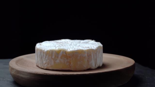 camembert-käse, der sich auf einer holzplatte auf dunklem hintergrund dreht - brie stock-videos und b-roll-filmmaterial