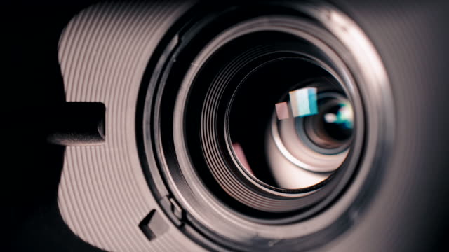Camera and lens Zoom, close-up photo, Closeup shot of professional video camera, with its lens zooming in and out.
