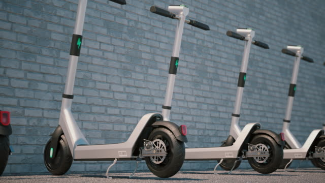 camera animation along of modern electric scooters parked in a row. - monopattino elettrico video stock e b–roll