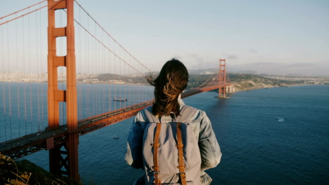 Camera approaches happy young local woman with backpack hiking, enjoying scenic sunset view at Golden Gate Bridge USA.