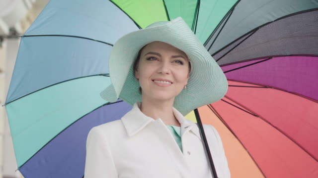 Camera approaches to elegant adult Caucasian woman standing outdoors with colorful umbrella and smiling. Portrait of charming beautiful mid-adult lady enjoying sunny day in city. Camera approaches to elegant adult Caucasian woman standing outdoors with colorful umbrella and smiling. Portrait of charming beautiful mid-adult lady enjoying sunny day in city. one mid adult woman only stock videos & royalty-free footage