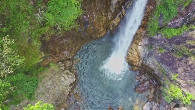 カメラは青い湖に走る滝taguに近づく - 崖点の映像素材/bロール