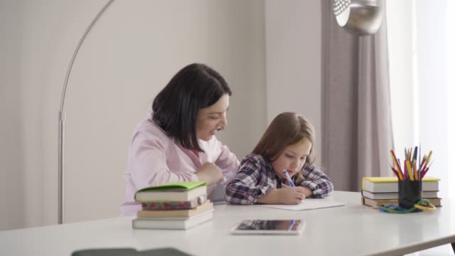 Camera approaching to tired Caucasian mother yawning as helping daughter to do homework. Cute brunette schoolgirl studying with mom at home. Support, education, intelligence.