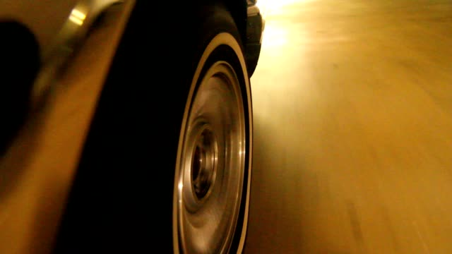 Camera attached on side of a car. Shot of car's wheel driving on parking lot video