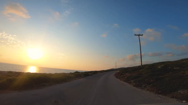 kamera bil front pov kör på panoramautsikt väg vid havet i zante vid solnedgången, grekland - bilperspektiv bildbanksvideor och videomaterial från bakom kulisserna