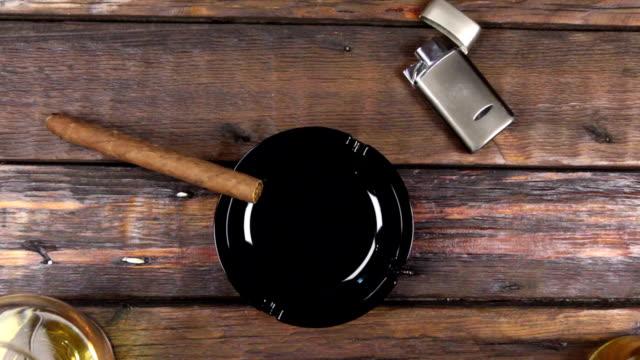 Camera crane, top view, modern wooden desk, glass of cognac and cigar .
