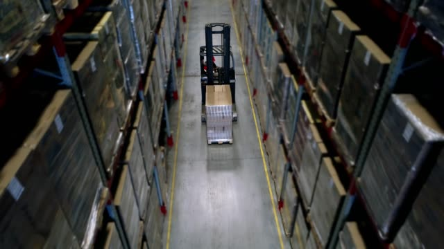 Camera cranes up on shelves of cardboard boxes inside a storage warehouse video