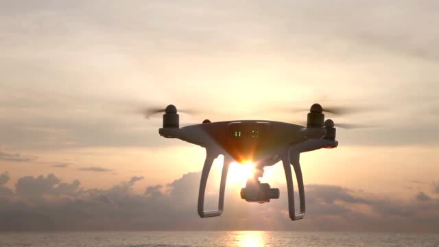 vídeos de stock, filmes e b-roll de câmera drone pairando no céu ao nascer do sol - avião sem piloto
