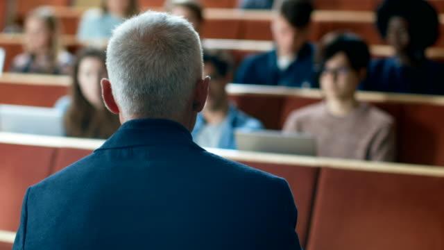 kamera mit blick auf klasse: college-professor hält einen vortrag zu einem klassenraum voller multi-ethnischen studenten. talentierte lautsprecher fängt die aufmerksamkeit des publikums. - dozenten stock-videos und b-roll-filmmaterial