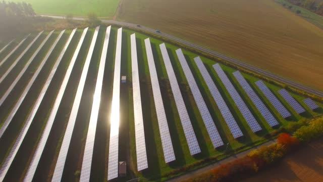 camera flight over a solar power station in sunset. - биомасса возобновляемая энергия стоковые видео и кадры b-roll