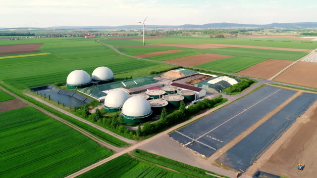 camera flight over biogas plant from pig farm. renewable energy from biomass. modern agriculture european union. aerial view, panoramic view from the air - биомасса возобновляемая энергия стоковые видео и кадры b-roll