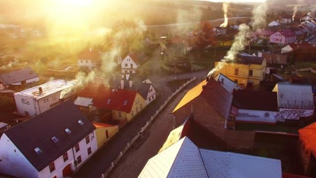 stockvideo's en b-roll-footage met de vlucht van de camera over tsjechische dorp in de winter. lokale verwarming is een belangrijke bron van uitstoot. luchtverontreiniging en klimaatverandering wijzigen thema. duurzame ontwikkeling en ecologie in de europese unie. - schoorsteen