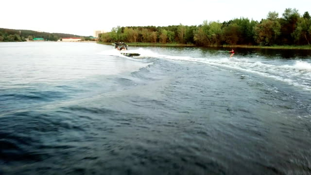 Camera follow behind wakeboarder surfing. Water extreme sport