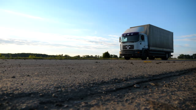 vídeos de stock e filmes b-roll de camera follow to truck driving on a highway. lorry rides through the countryside with beautiful landscape at background. slow motion side view - driveway, no people