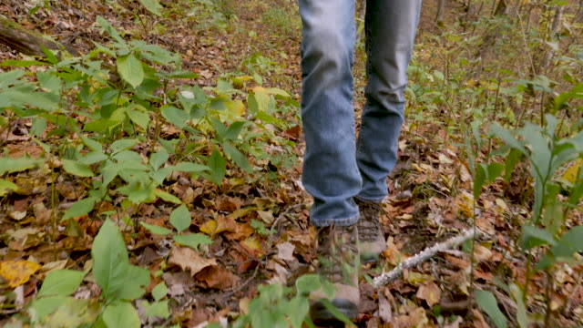 Camera following a man wearing jeans and hiking boots walking forward
