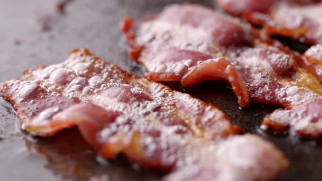 Camera follows cooking bacon on grill. Bacon dolly in slow motion. Camera follows cooking bacon on grill. Bacon dolly in slow motion. bacon stock videos & royalty-free footage