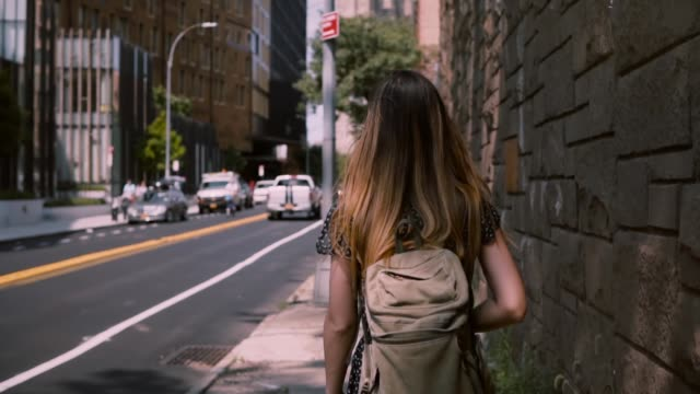 camera follows european brunette woman with long flying hair walking along big red brick building wall, slow motion - city walking background video stock e b–roll
