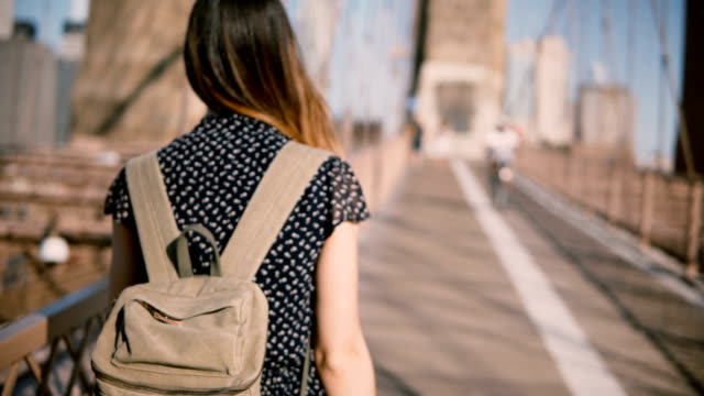 camera follows female tourist with backpack and dark golden hair walking along brooklyn bridge on a clear sunny day 4k - city walking background video stock e b–roll