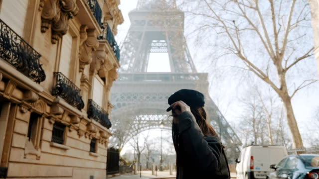 Camera follows happy beautiful woman excited to see Eiffel Tower, posing and smiling on autumn Paris street slow motion. video