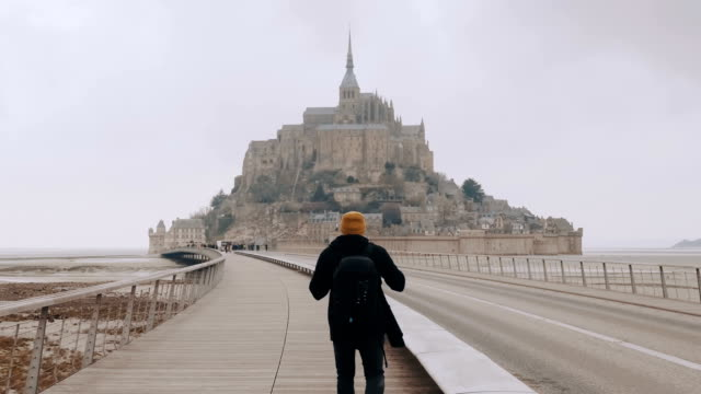 camera follows happy excited tourist man with backpack walking to epic mont saint michel castle in normandy slow motion. - manica video stock e b–roll