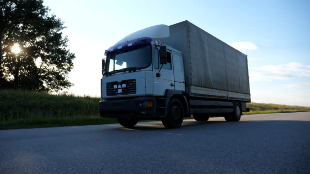 vídeos de stock e filmes b-roll de camera follows to truck driving on a highway. lorry rides through the countryside with beautiful landscape at background. side view slow motion close up - driveway, no people