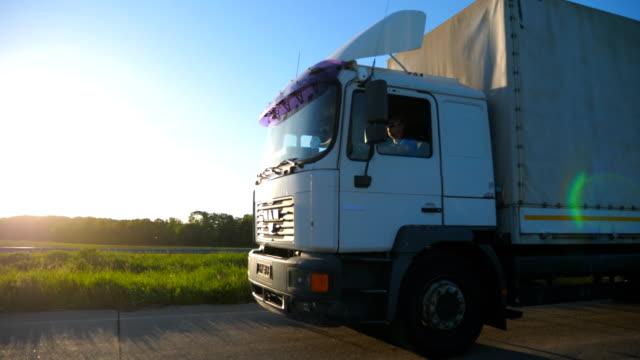 kameran följer lastbil med last trailer körning på motorväg och transportera varor. vit lastbil fortkörning genom landsbygden väg vid solnedgången tid. vacker bakgrund. sidoläge för slow motion - shipping sunset bildbanksvideor och videomaterial från bakom kulisserna