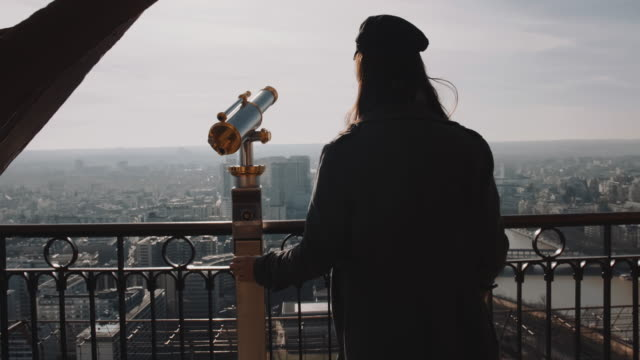 Camera follows young happy attractive blogger woman smiling at view point on top of Paris Eiffel Tower slow motion.