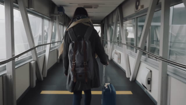 Camera follows young happy tourist woman walking along modern airport departure hall corridor with suitcase slow motion. video