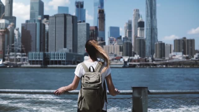 Camera follows young happy traveler girl with backpack, jumping with arms wide open at Manhattan skyline in New York video