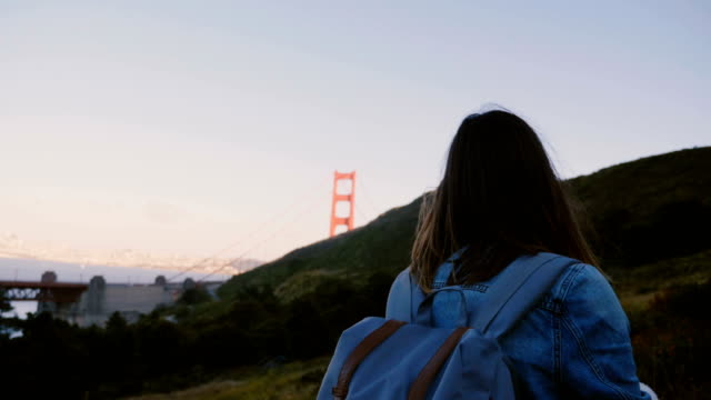 Camera follows young tourist woman with backpack hiking up large hill to enjoy epic sunset view of Golden Gate Bridge.