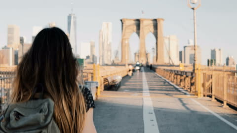 Camera follows young woman with backpack walking along Brooklyn Bridge, New York on a beautiful sunny summer day 4K Camera follows young woman with backpack walking along Brooklyn Bridge, New York on a beautiful sunny summer day 4K. Happy female tourist with long hair blowing in the wind enjoying urban scenery. famous place stock videos & royalty-free footage