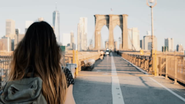 Camera follows young woman with backpack walking along Brooklyn Bridge, New York on a beautiful sunny summer day 4K video